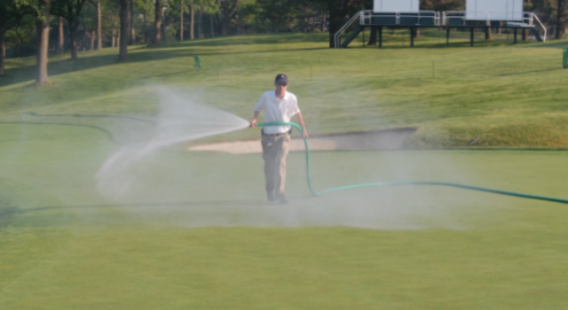 man watering a golf green